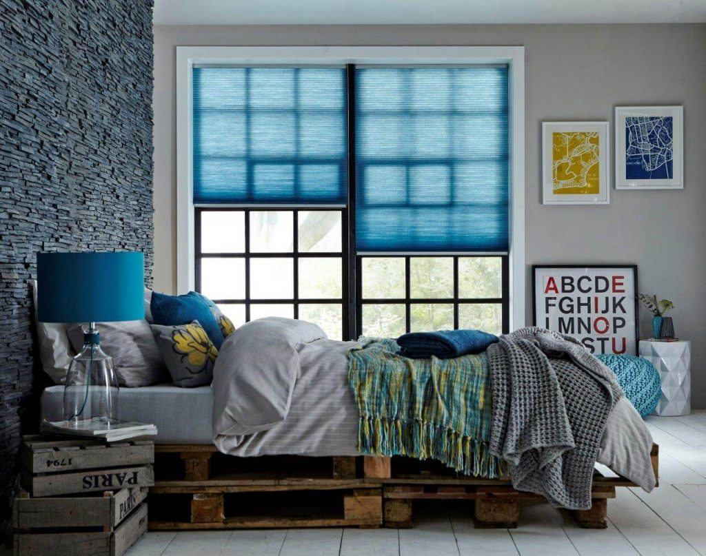 Blue pleated blinds in a bedroom window