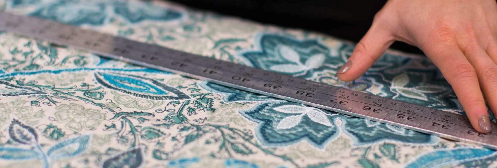 Cutting and measuring designer fabric to make curtains at Fabric Gallery and Interiors curtain workroom