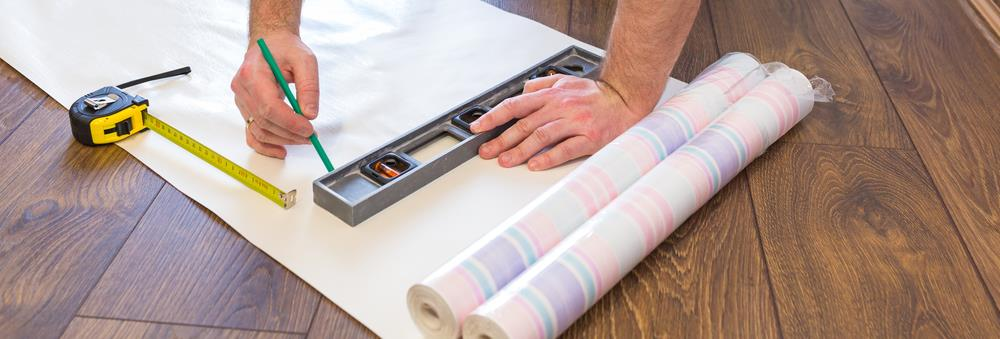 Image of person measuring wallpaper before cutting